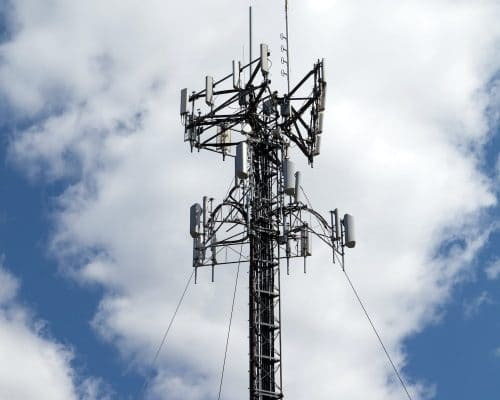A cellular antenna tower isolated over a blue sky with white fluffy clouds.